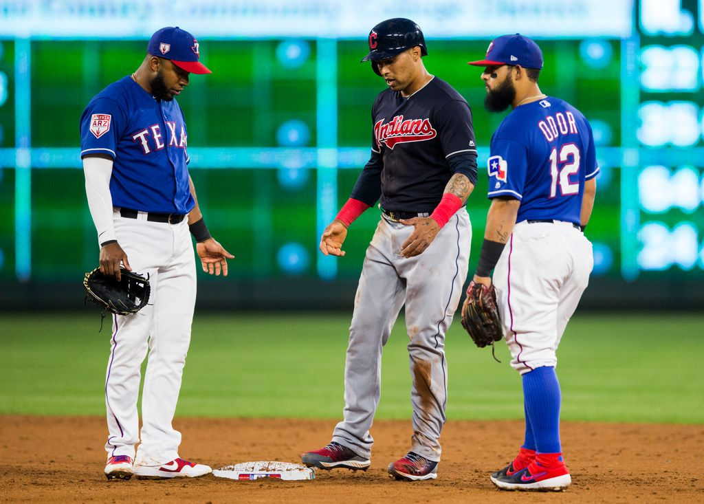 Texas Rangers shortstop Elvis Andrus (1) and second baseman Rougned Odor (12) give Cleveland Indians designated hitter Hanley Ramirez (2) a hard time at second base during the third inning of a spring training baseball game between the Texas Rangers and the Cleveland Indians on Monday, March 25, 2019 at Globe Life Park in Arlington. (Ashley Landis/The Dallas Morning News)