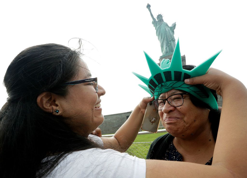 Karen Mejia (left) fits her mother, Leonor Chipayo, with a souvenir Statue of Liberty foam visor while visiting the Statue of Liberty on Aug. 14, 2019, in New York. Both women are from Lima, Peru. Long before a Trump administration official suggested the poem inscribed on the Statue of Liberty welcomed only people from Europe, the words captured America's promise to newcomers at a time the nation was also seeking to exclude many immigrants from landing on its shores.  (AP Photo/Kathy Willens)