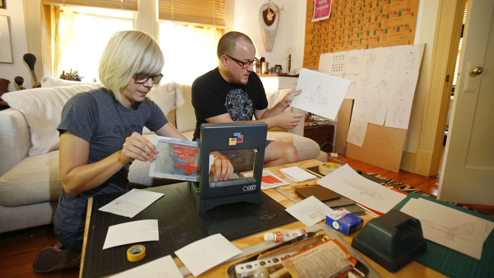 "Artists Gwen McGinn and Isaac Cohen make postcards to advertise the inaugural issue of ""The Dallas Coloring Book Experiment"" zine for the first-ever Dallas Zine Party on Sept. 6. They are photographed screen printing in Cohen's home in Dallas."