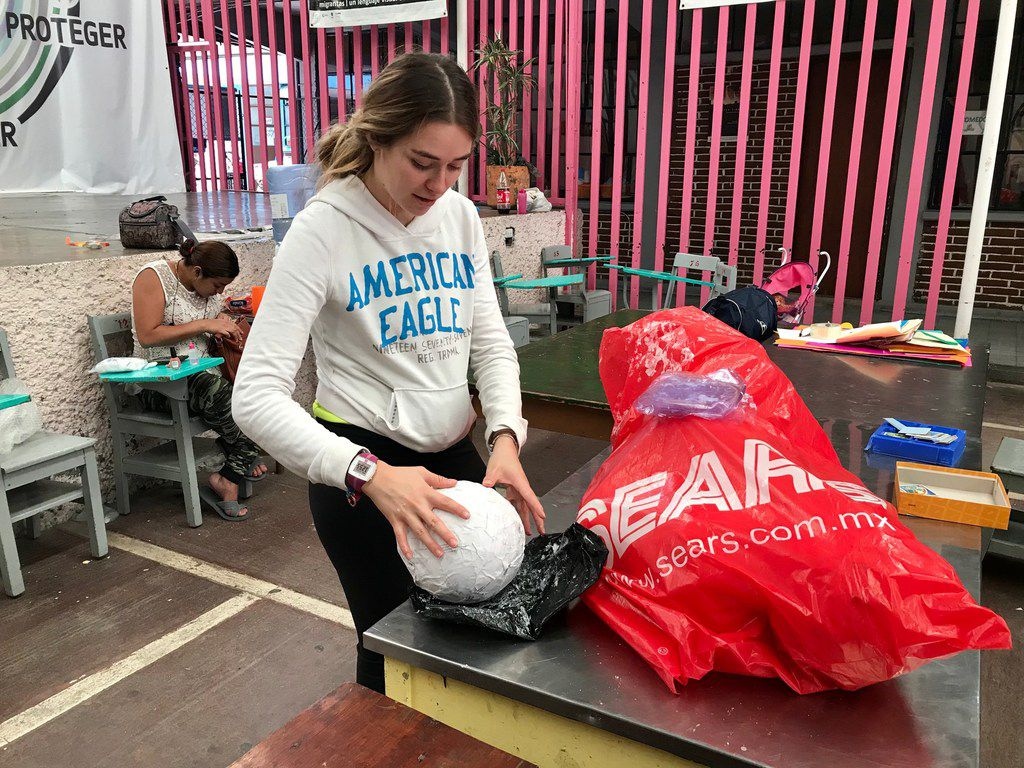 Isabella Mariel, a volunteer at the Casamin shelter in Mexico City, teaches migrants basic skills like cooking, sewing and crafts.