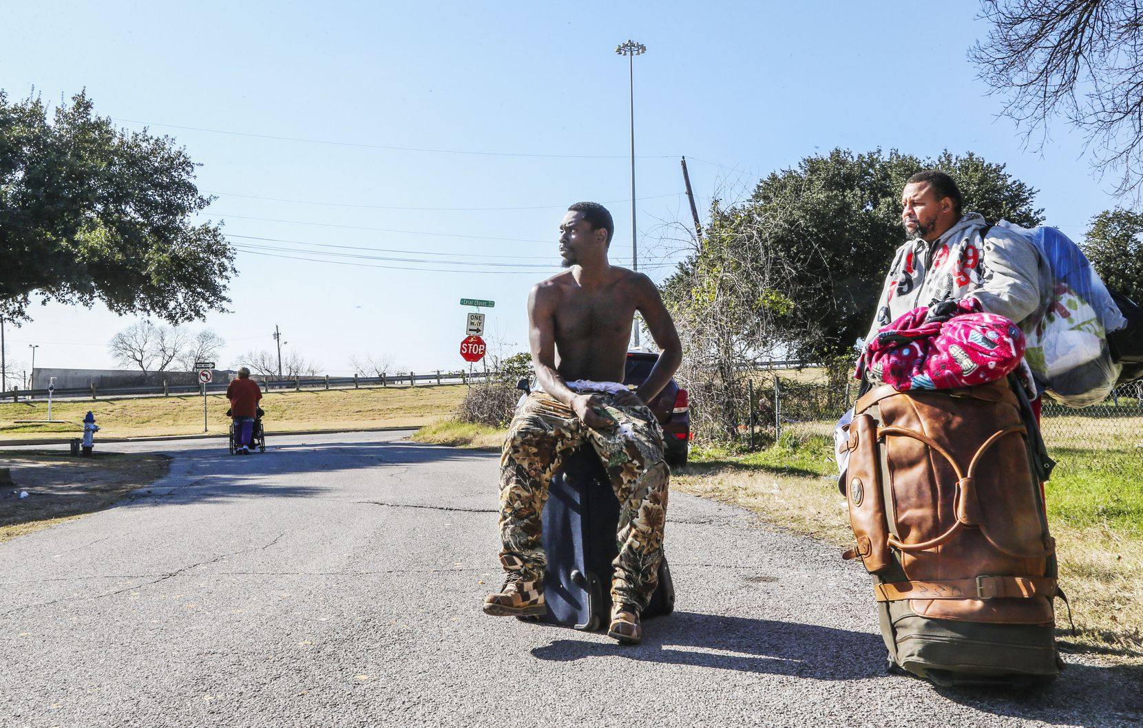 Chris Johnson (left) and Carlton Nalley, who are both homeless, carry their belongings after leaving  Our Calling in Dallas on Dec. 10, 2018.