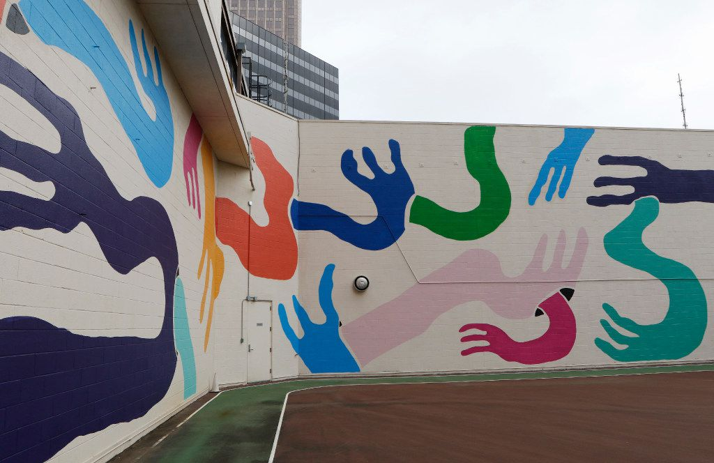 "Muralist Kyle Steed completed his mural, working title, ""Hands All In,"" at the Plaza of the Americas building in downtown Dallas. (David Woo/The Dallas Morning News)"