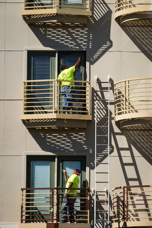 Painters work on trim and railing at the Phoenix Midtown apartments on Mockingbird on Frida. The deco murals on the property, painted by Jeff Garrison and Chris Arnold in 2008, have been painted over with solid beige. (Smiley N. Pool/The Dallas Morning News)