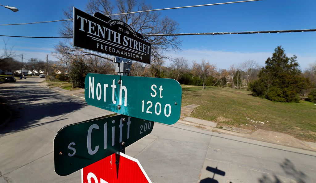 A street sign topper reminds residents of the historic Tenth Street Freedmanstown east of I-35E in the Oak Cliff area of Dallas. North Street homes in the background have been torn down. There is a federal lawsuit over the demolition of the decrepit Tenth Street Historic District.