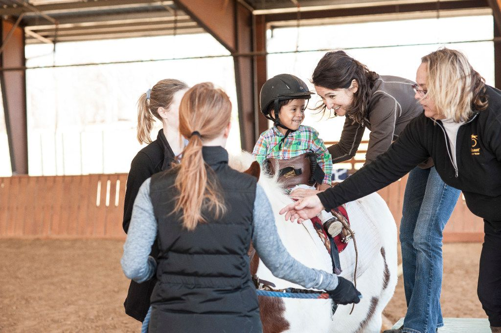 Equest workers and volunteers Kristi Immitt, Jen Donahue, Yvette LeBlanc and Jessica Cline help Matthew ride a horse.