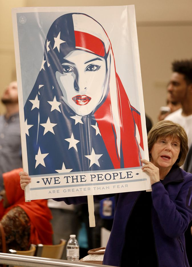 Cheryl Pollman holds a sign during a protest against Pres. Donald Trump's executive order banning people entry to the U.S. from specific countries at Terminal D at Dallas/Fort Worth International Airport in Dallas, Saturday, Jan. 28, 2017. (Jae S. Lee/The Dallas Morning News)
