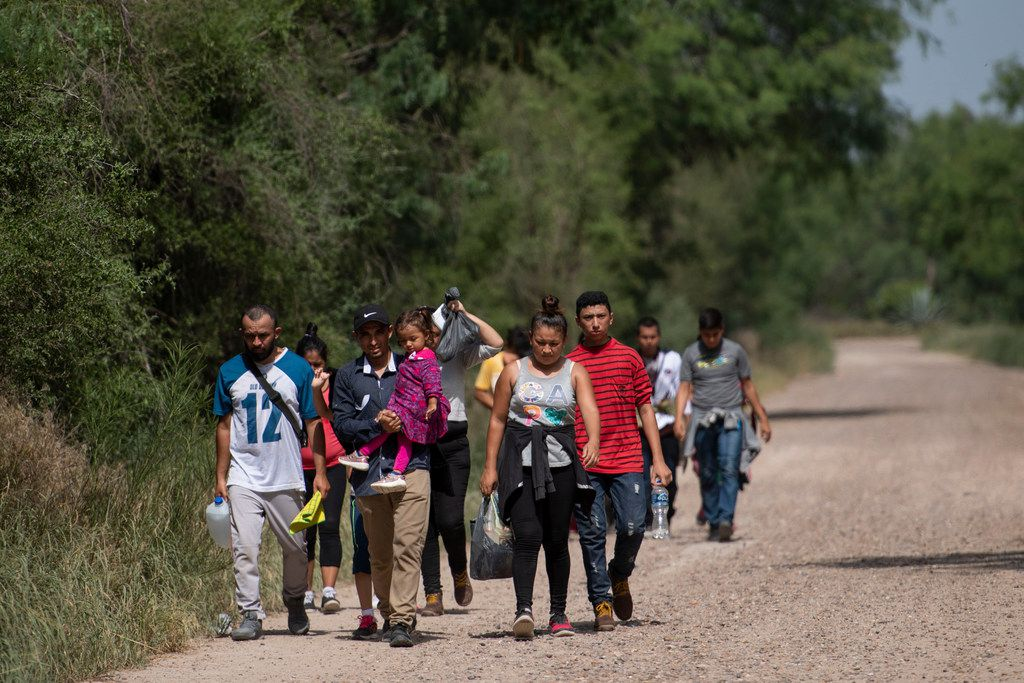 Hours after officials toured the border area of South Texas, migrant families walk toward U.S. Border Patrol agents for processing on June 20, 2019.