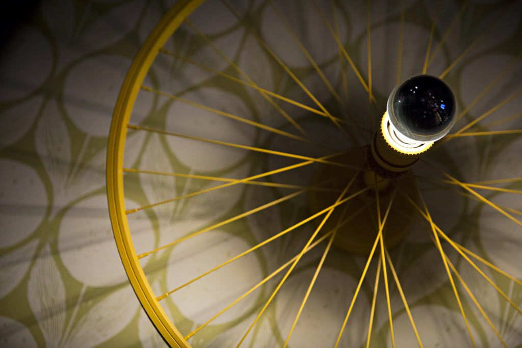 A bicycle wheel turned into a light fixture at The Royale Magnificent Burgers Thursday, February 18, 2016 in Plano, Texas. (G.J. McCarthy/The Dallas Morning News)