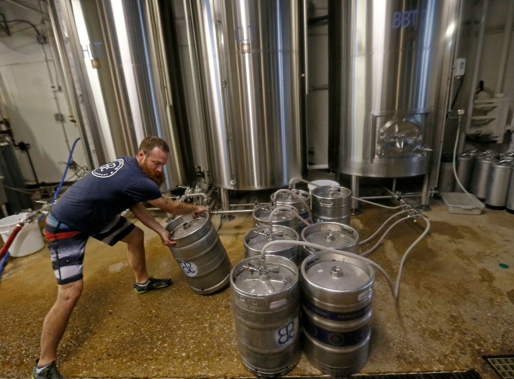 Brewer Rich Franzen moves one of the kegs being filled with beer at Peticolas Brewing Co. No job is too big or too small for the brewers here .