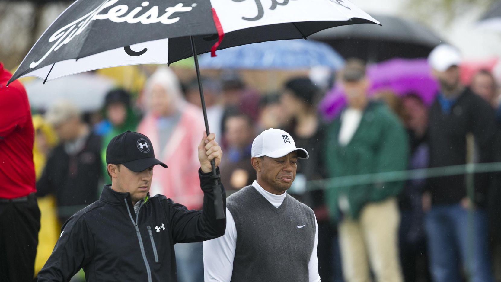 Jan 30, 2015; Scottsdale, AZ, USA; PGA golfer Jordan Spieth holds an umbrella as he walks with PGA golfer Tiger Woods on the sixth hole during the second round of the Waste Management Phoenix Open at TPC Scottsdale. Mandatory Credit: David Wallace-Arizona Republic via USA TODAY Sports