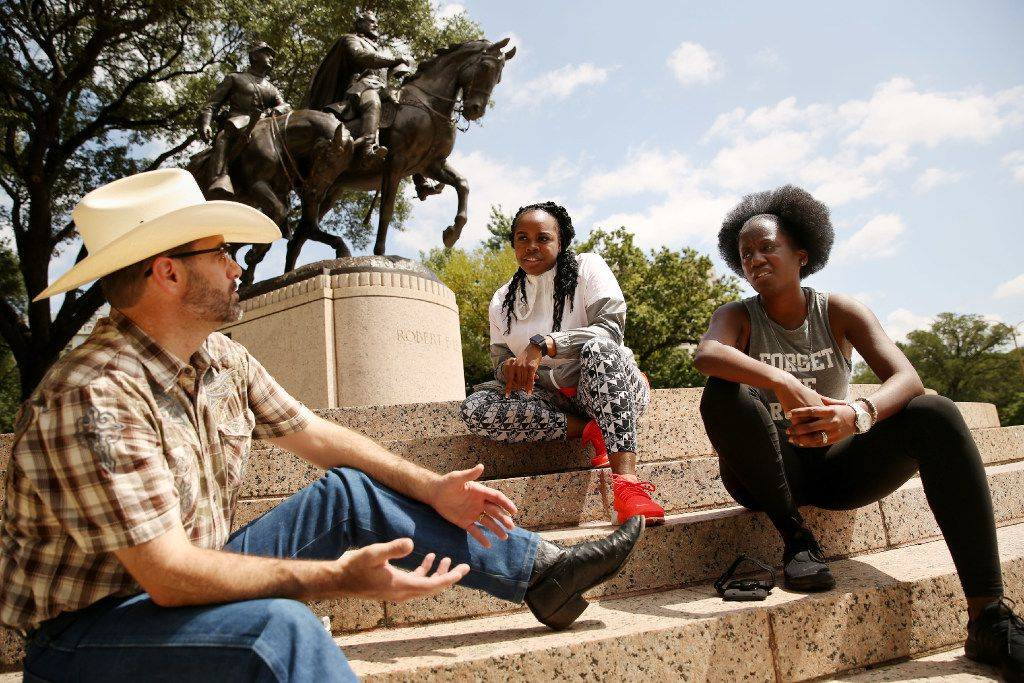 From left:  Daniel Shipman, Adria Green and Crystal Sentell, all of Dallas, have a conversation about race, racism and Civil War history near a statue of Confederate Gen. Robert E. Lee at Lee Park in the Oak Lawn neighborhood of Dallas on Wednesday.