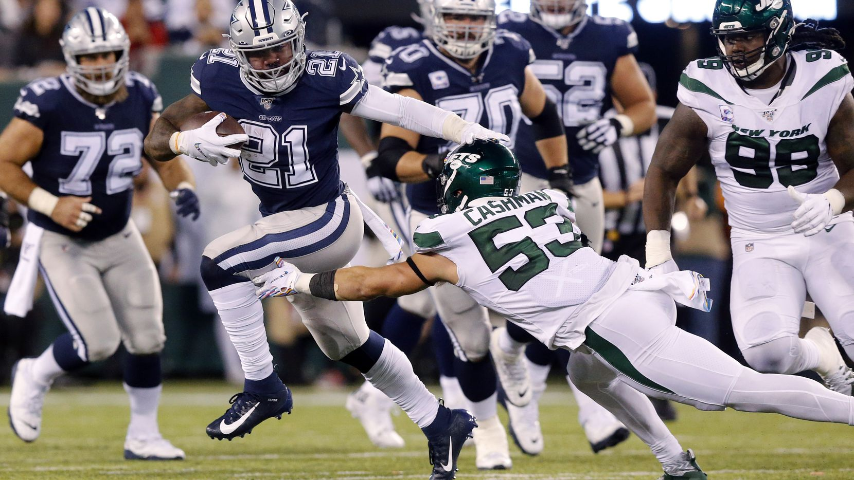 Dallas Cowboys running back Ezekiel Elliott (21) avoids the diving tackle attempt by New York Jets linebacker Blake Cashman (53) at MetLife Stadium in East Rutherford, New Jersey, Sunday, October 13, 2019.
