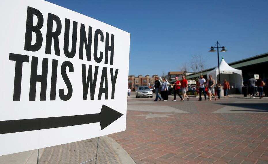 People walk by a sign during Morning After Brunch Festival at Dallas Farmers Market in Dallas, Saturday, Feb. 11, 2017.