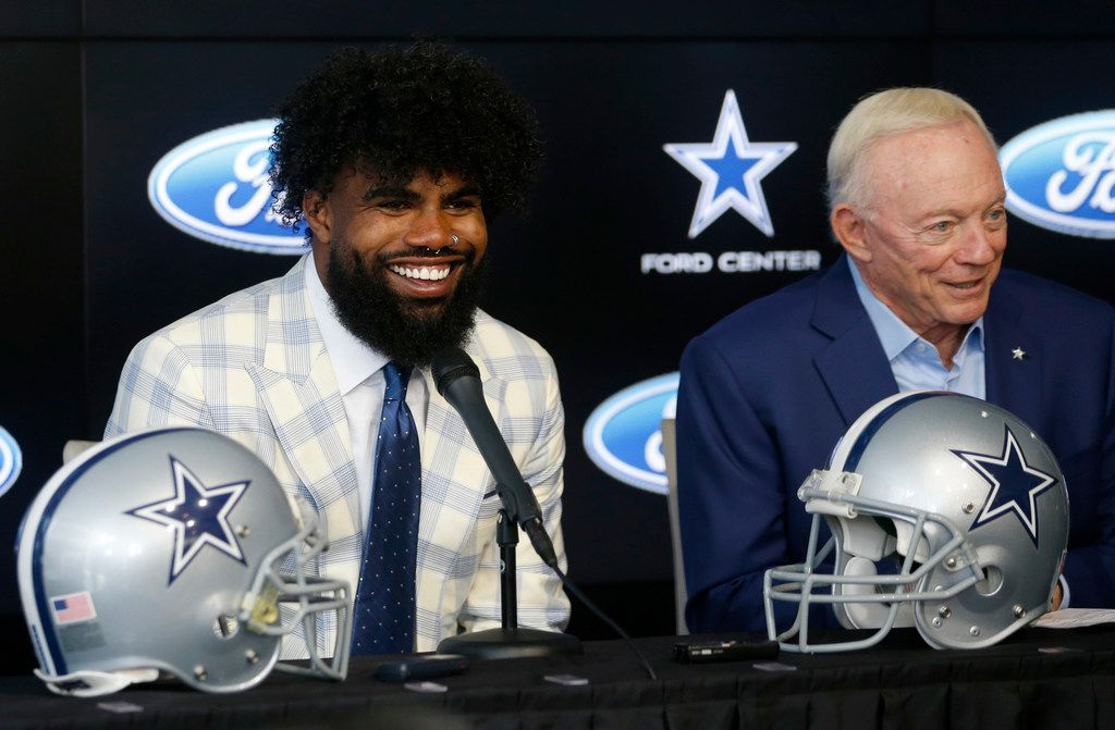 Dallas Cowboys running back Ezekiel Elliott (21) smiles as he sits next to Dallas Cowboys owner and general manager Jerry Jones during a press conference about Elliott's contract extension at The Star in Frisco, Texas on Thursday, September 5, 2019. (Vernon Bryant/The Dallas Morning News)
