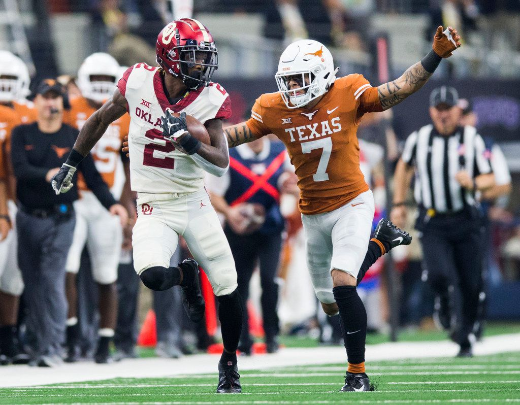 Oklahoma Sooners wide receiver CeeDee Lamb (2) runs the ball ahead of Texas Longhorns defensive back Caden Sterns (7) during the second quarter of the Big 12 Championship football game between the Texas Longhorns and the Oklahoma Sooners on Saturday, December 1, 2018 at AT&T Stadium in Arlington, Texas. (Ashley Landis/The Dallas Morning News)