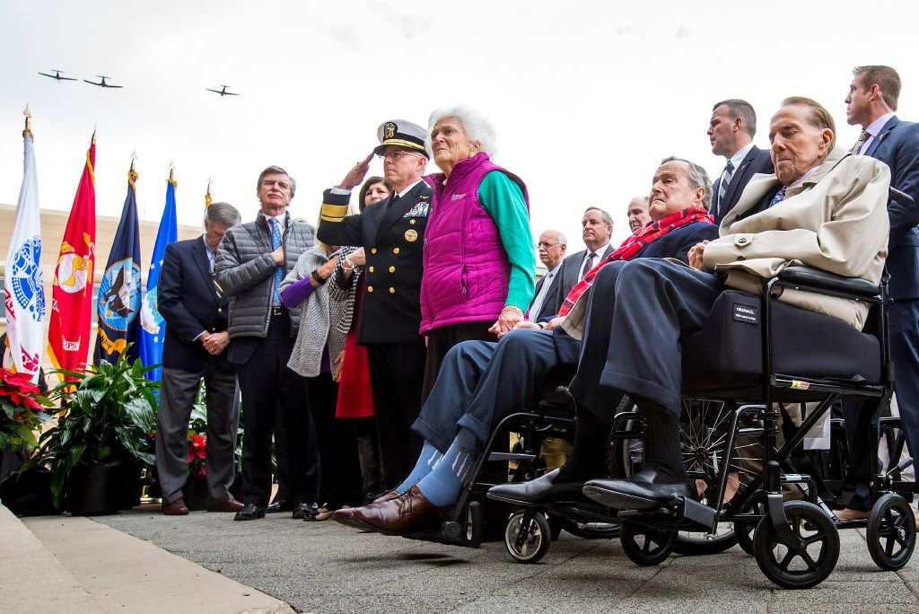 Adm. Chip Miller, former commanding officer of the USS George H.W. Bush, and former first lady Barbara Bush stood beside former President George H.W. Bush and former U.S. Sen. Bob Dole as vintage aircraft flew overhead during the playing of taps at a Pearl Harbor 75th anniversary commemoration at the George Bush Presidential Library on Wednesday, Dec. 7, at Texas A&M in College Station. (Smiley N. Pool/The Dallas Morning News)