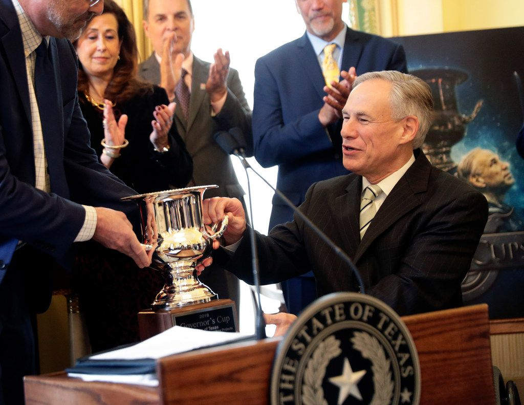 Texas Gov. Greg Abbott, right, is presented the Governor's Cup by Site Selection Magazine during a news conference at the Texas Governor's Mansion, Monday, March 4, 2019, in Austin, Texas. Texas won for having the most qualified projects of any state according to their data. (AP Photo/Eric Gay)