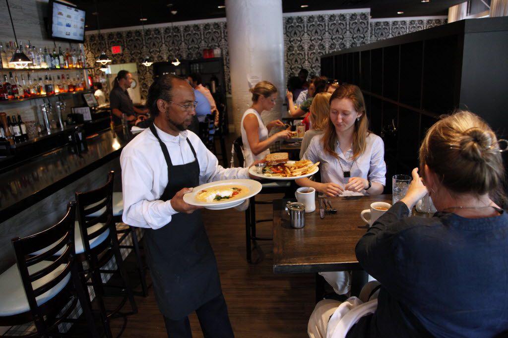 Server Richard Pruitt serves patrons lunch at Ellen's Southern Kitchen in the West End in Dallas on June 5, 2013. (Sonya Hebert-Schwartz/The Dallas Morning News)