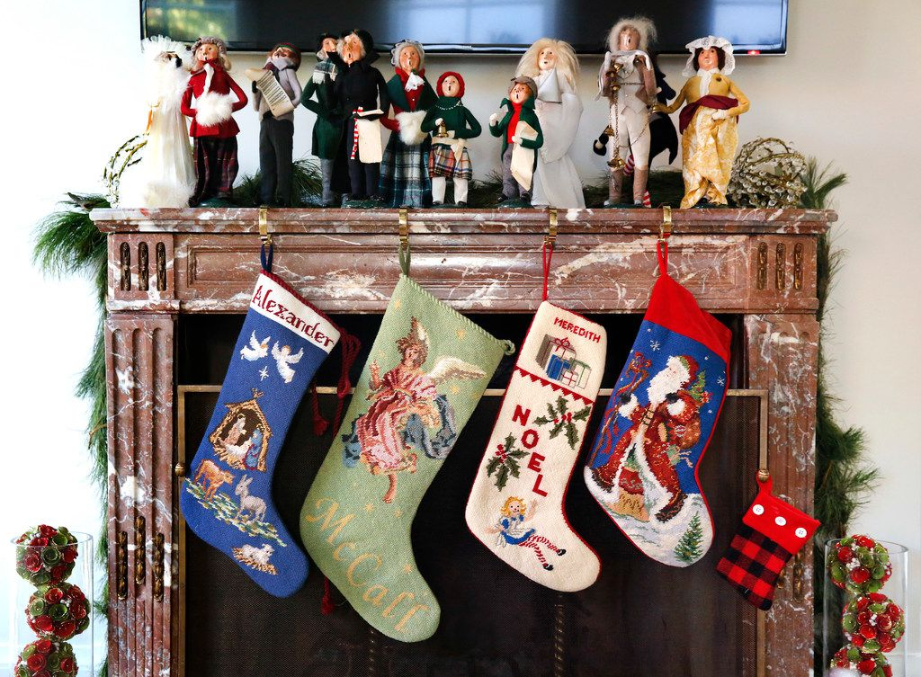 The needlepoint stockings were hung with care at Land's Dallas home, which she has filled with meaningful family pieces, including the caroler collection on the fireplace.