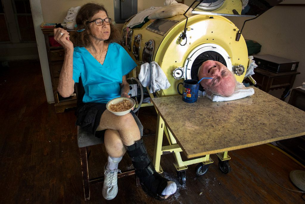 Paul Alexander chats with caregiver and friend Kathryn Gaines as he drinks coffee and she eats breakfast beside his iron lung.