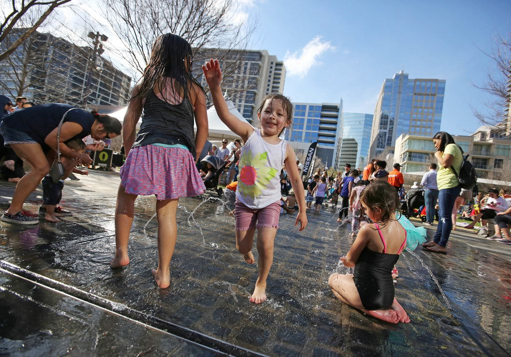Children of all ages enjoy the spray park fountain during  at Klyde Warren Park in downtown Dallas.