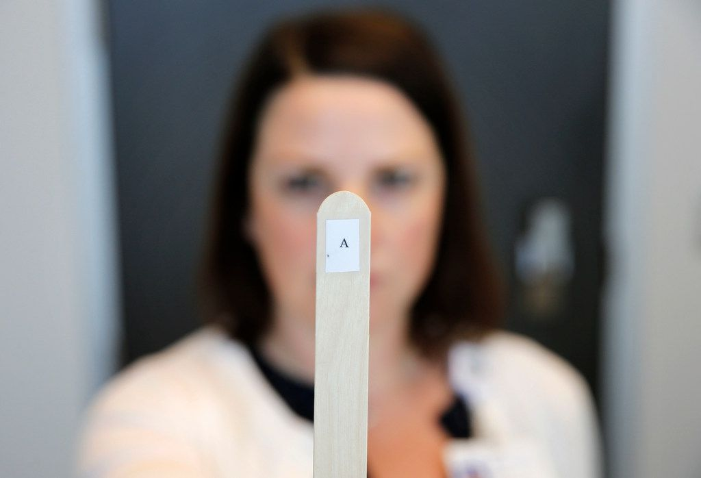 """Dr. Erin Reynolds, a neuropsychologist, holds up a tongue depressor with an """"A,"""" printed on it to test patients enrolled in Baylor Scott & White Sports Concussion Program in Frisco."""