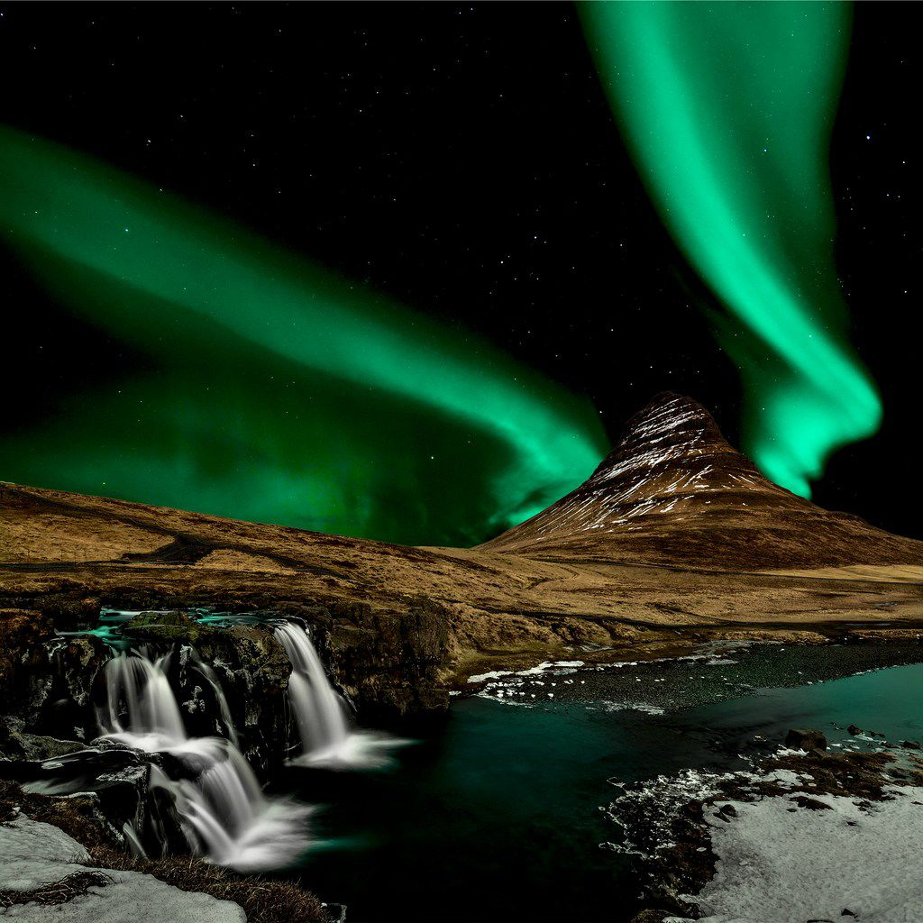 The northern lights illuminate the night sky over Iceland's impressive landscape in this composite photo.