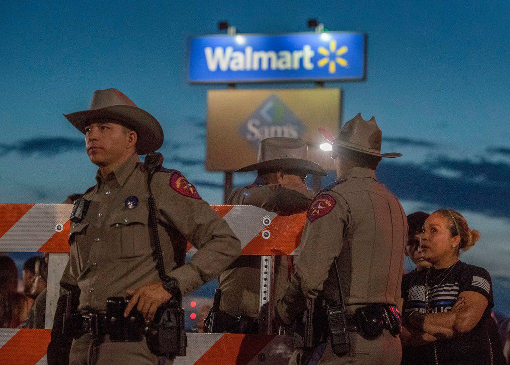 Texas State Troopers keep watch at the makeshift memorial for victims of the shooting that left a total of 22 people dead at the Cielo Vista Mall Walmart in El Paso.