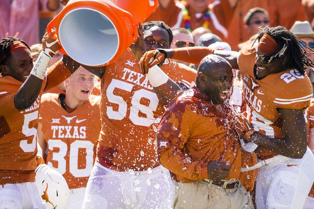 Texas head coach Charlie Strong hugs safety Adrian Colbert (26) after he is doused with a bucket of ice water as the Longhorns celebrates a 24-17 victory over Oklahoma in the 2015 Red River Showdown NCAA football game at the Cotton Bowl on Saturday, Oct. 10, 2015, in Dallas.