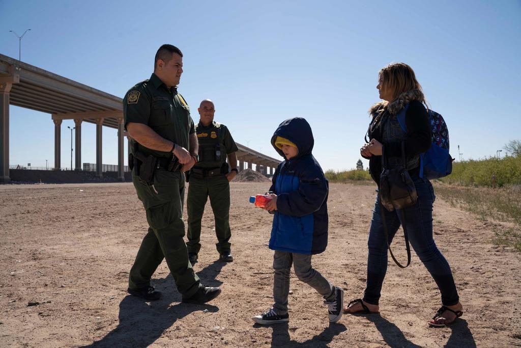 Una madre y su hijo se entregan ante un agente de la Patrulla Fronteriza para peticionar por asilo en El Paso. Con sus centros de procesamiento saturados, las autoridades de inmigración están empezando a liberar a muchos migrantes. (AFP/GETTY IMAGES/PAUL RATJE)