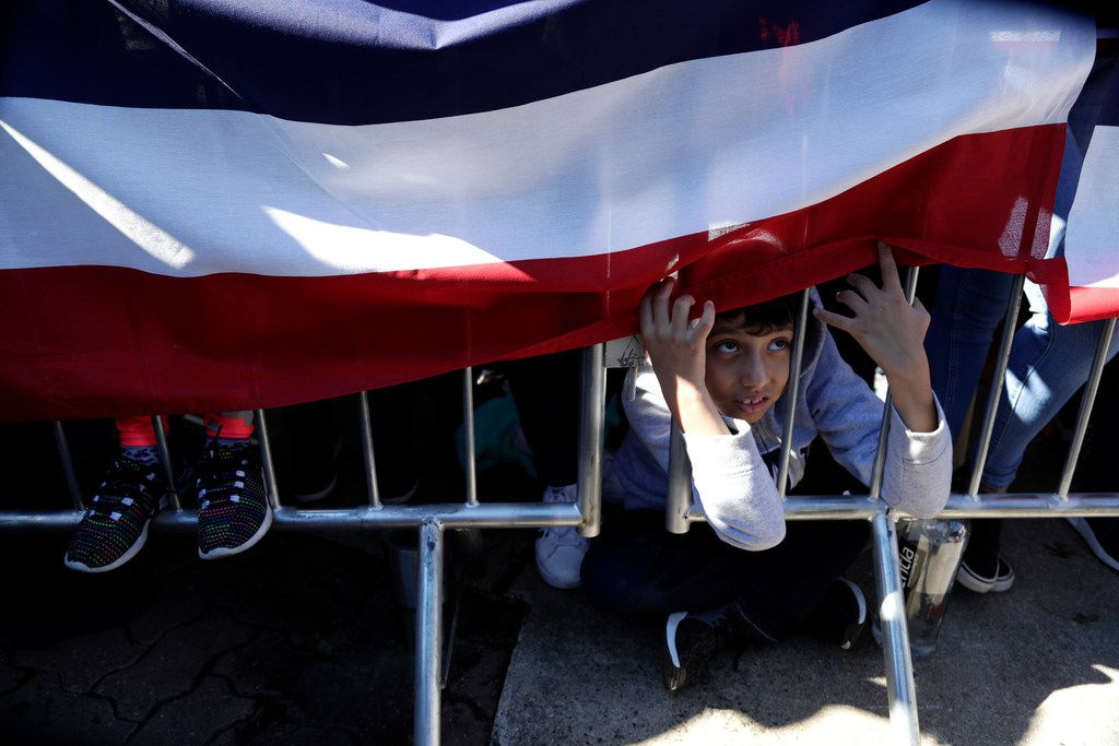 A young boy peeks under a banner as he watches former San Antonio Mayor and Housing and Urban Development Secretary Julian Castro make his announcement to seek the 2020 Democratic presidential nomination, Saturday, Jan. 12, 2019, in San Antonio. (AP Photo/Eric Gay)