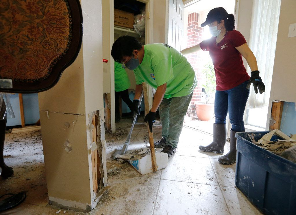 John Truong and Thi Dang work on cleaning the foyer at the home of Chan Van Nguyen in Katy on Monday.