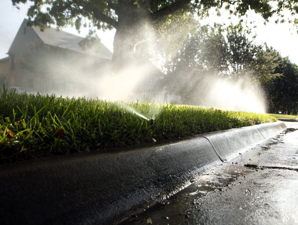 Sprinklers water the lawn -- with spray also going into the street gutter -- in front of a house in the 4100 block of University Blvd. in University Park, Texas on Monday morning, July 16, 2012. (Brad Loper/The Dallas Morning News) / lawn, watering, water restrictions, watering restrictions, landscape, drought, water use / 07282012xNEWS 07282012xBRIEFING 07292012xNEWS