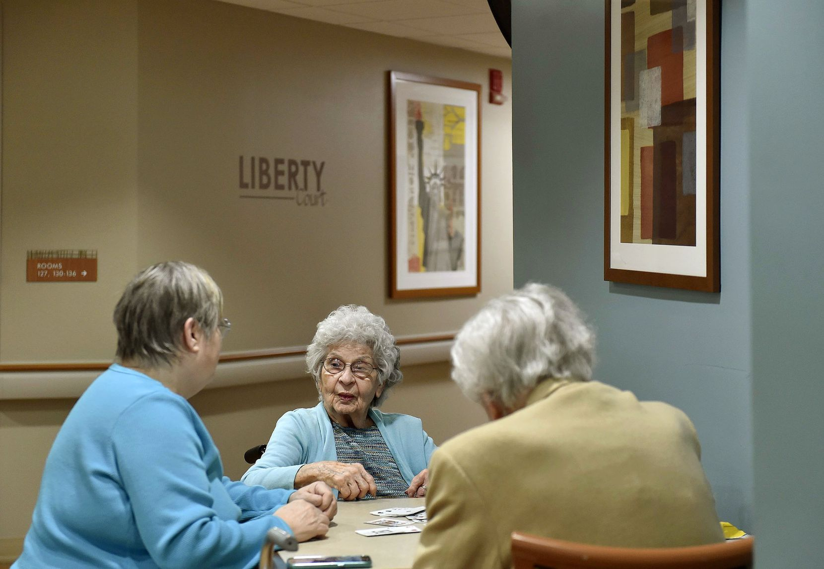Phylas Lose, center, plays cards with her daughter Jan Morehead (left) and a friend at Lakeview Village in Lenexa, Ark. Medicare's Nursing Home Compare website gives Lakeview Village five stars in all categories.