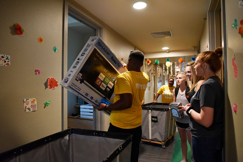 Student volunteer Joseph Lashley carries a flat screen TV for incoming freshman Makinley Eddlemon (right), 18,as she moved into the UNT-Dallas dorm.
