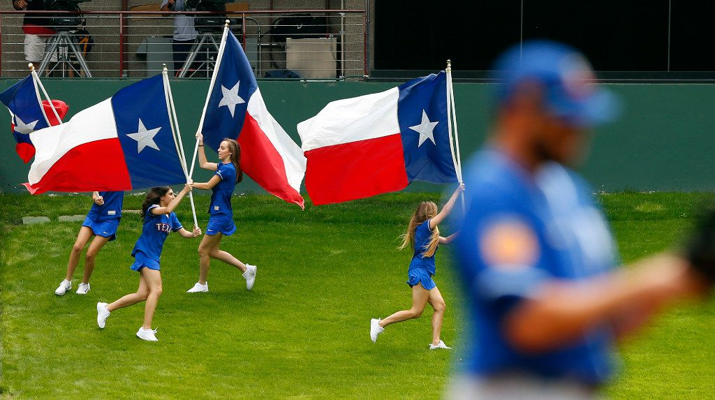 The Rangers Texas flag bearers race around the grassy knoll after Delino DeShields scored the first run of the game against the Kansas City Royals during the first inning at Globe Life Park in Arlington, Texas, Saturday, April 1, 2017. The Rangers were playing the Royals in an exhibition game. (Tom Fox/The Dallas Morning News)