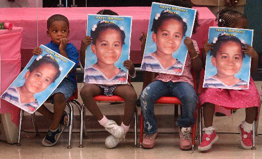 Children hold posters of Rilya Wilson, a 4-year-old in foster care in Florida who was missing for months before authorities noticed. Her foster parent is in prison for her killing.