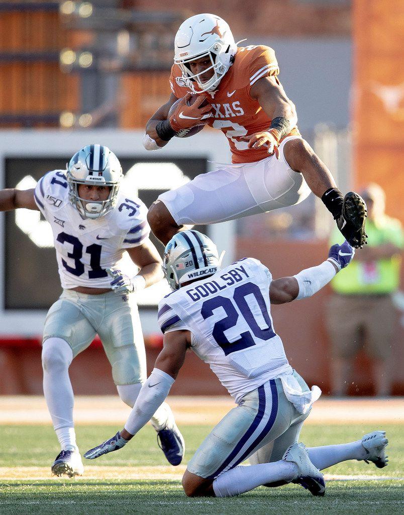Texas running back Roschon Johnson (2) hurdles Kansas State defensive back Denzel Goolsby (20) during an NCAA college football game Saturday, Nov. 9, 2019, in Austin, Texas. (Nick Wagner/Austin American-Statesman via AP)