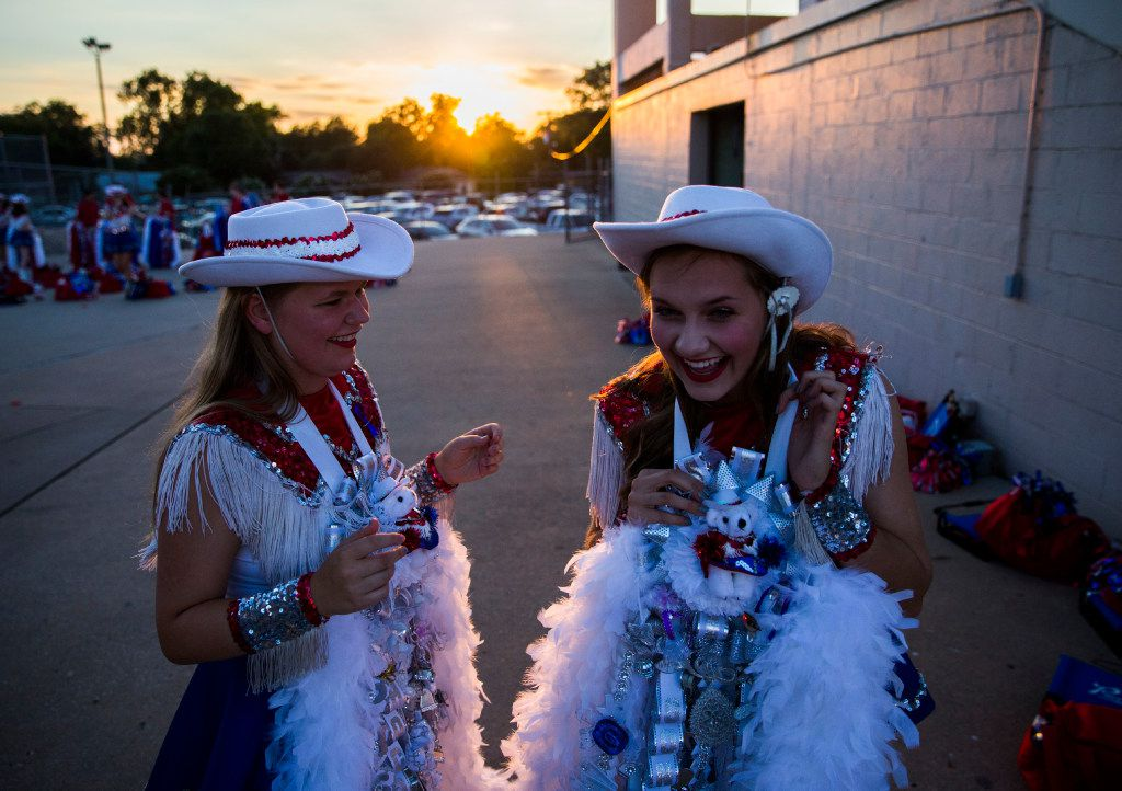 Richardson Pearce Pacesetters member Andre Ujcich, left, helps Hope Winters, right, with her homecoming mum before their game against Richardson on Sept. 23 at Eagle Mustang Stadium in Richardson.