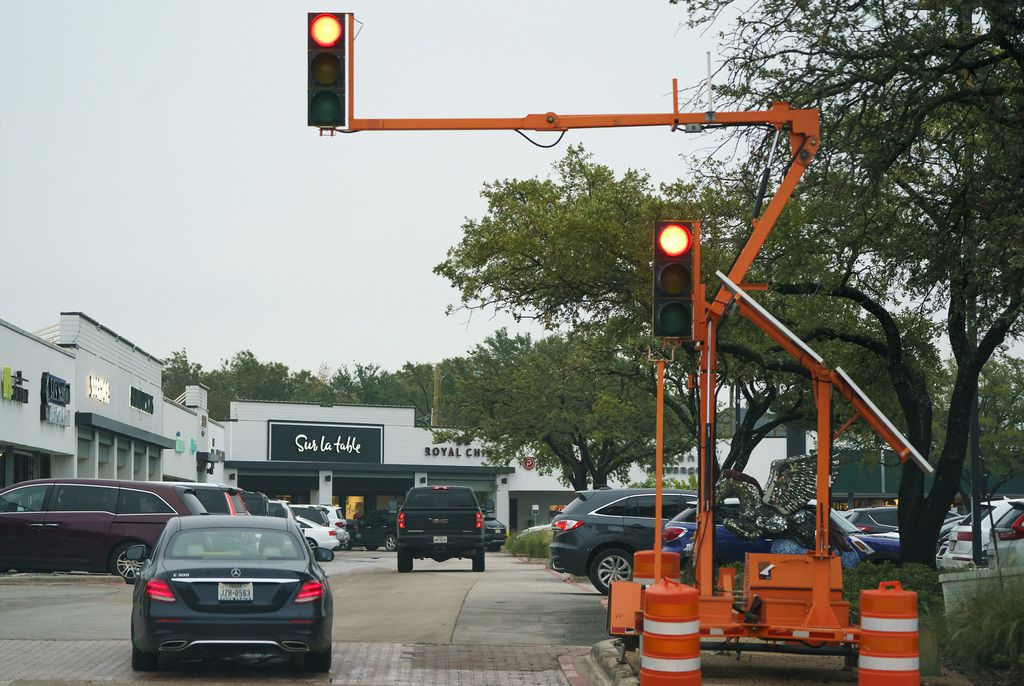 Temporary traffic signals are seen at a parking entrance on the northeast corner of the Preston Royal Shopping Center, which was damaged by October's tornadoes.