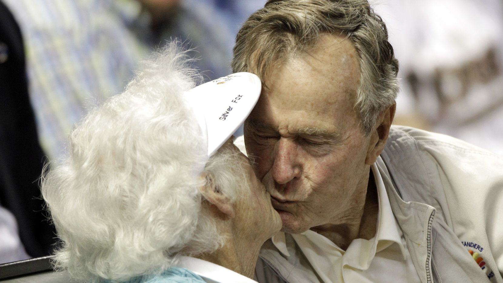 """FILE - In this May 5, 2010 file photo, former U.S. President George H.W. Bush, right, kisses his wife, Barbara, after both were shown on the stadium kiss cam video board during the sixth inning of a baseball game against the Arizona Diamondbacks in Houston. Former first couple George and Barbara Bush's relationship is a true love story, described by granddaughter Jenna Bush Hager as """"remarkable."""" They met at a Christmas dance. She was 17. He was 18. Two years later they were married. Now 73 years later, with Barbara Bush declining further medical care for health problems, they are the longest-married couple in presidential history. (AP Photo/David J. Phillip, File)"""