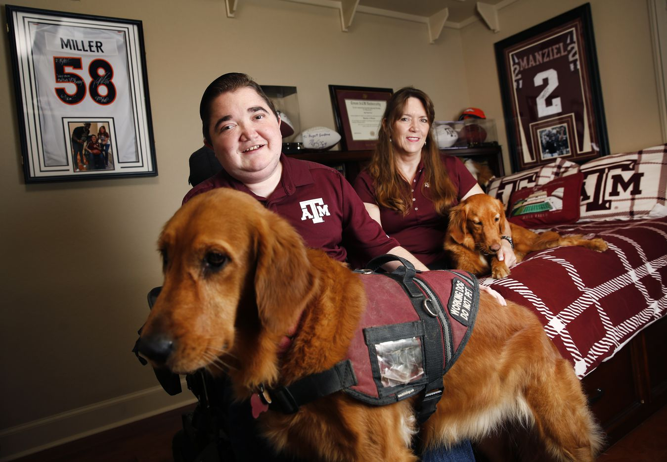 Texas A&M graduate student Kyle Cox (left), who has Duchenne muscular dystrophy, poses with his female golden retriever service dog, Amber, and his mother, Kristen Cox and Abby, another adopted retriever, in his A&M themed bedroom in College Station, Texas, Wednesday, September 11, 2019. Amber wasn't adopted from the A&M research laboratory where they test dogs with Duchenne, but Abby was.
