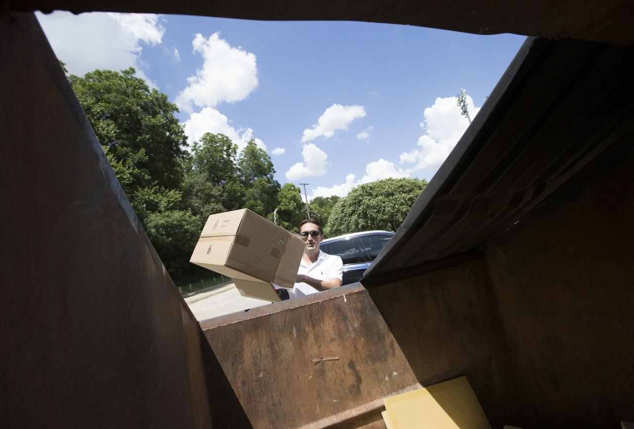 José Cavazos, de Dallas, bota material reciclable en un basurero para reciclaje en el parque Reverchon. (DMN/TING SHEN)