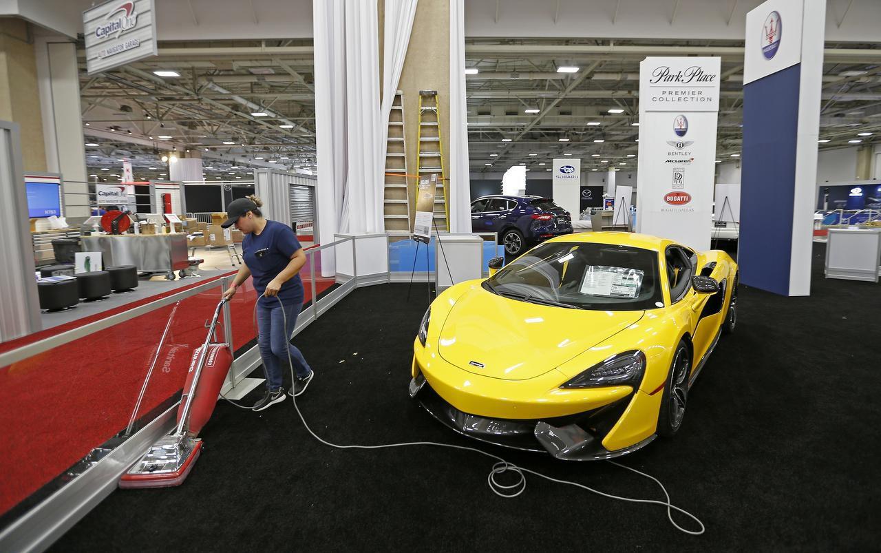 Norma Ayala limpia la alfombra del Kay Bailey Hutchinson Convention Center junto a un 2017 McLaren 570S Coupe.