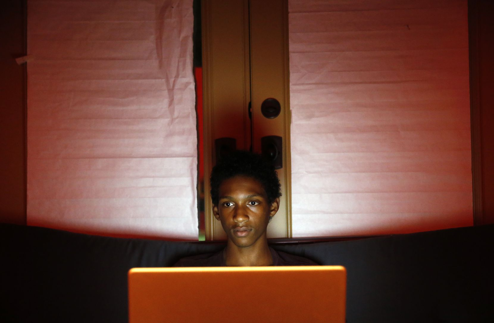 Joshua Waters uses his laptop during a bit of downtime at home in Dallas. (Vernon Bryant/Staff Photographer)