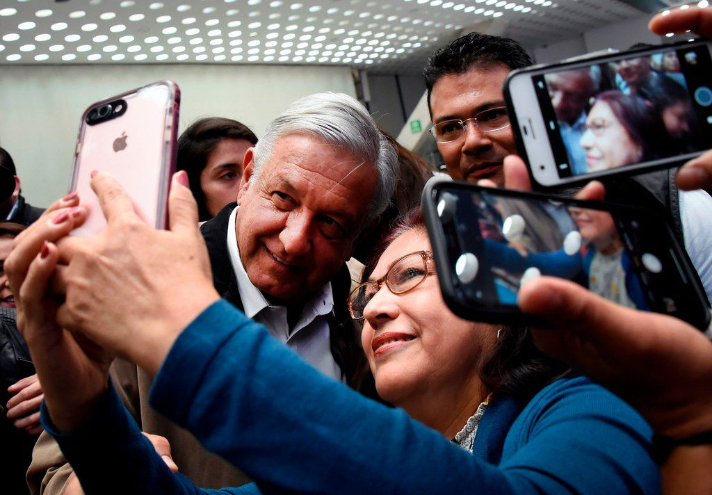 Mexican President Andres Manuel Lopez Obrador poses for a selfie with a passenger at Mexico City's international airport on February 15, 2019.