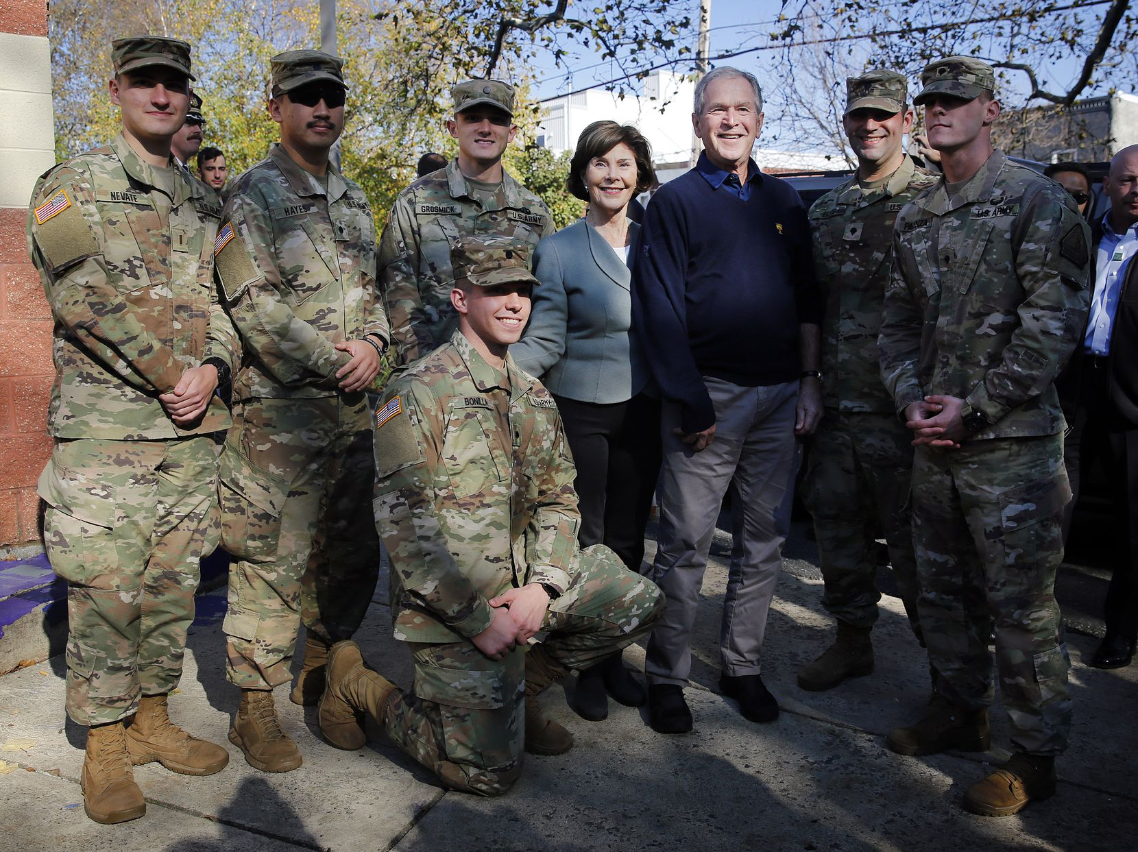 Former President George W. Bush and former first lady Laura Bush joined serviceman for a group photo before leaving Wharton Square in the Point Breeze neighborhood of Philadelphia on Sunday. Veterans who serve as Character Does Matter mentors for the Travis Manion Foundation planted a pair of dogwood trees and worked on landscaping projects in the neighborhood for Veterans Day.