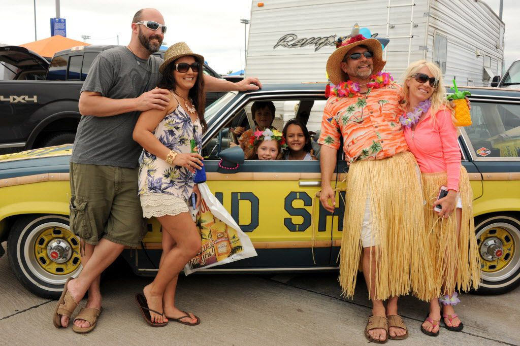 Buffett fans gather around a station wagon painted with the Land Shark Beer logo at the Jimmy Buffett tailgate party at Toyota Stadium in Frisco, TX on May 30, 2015.