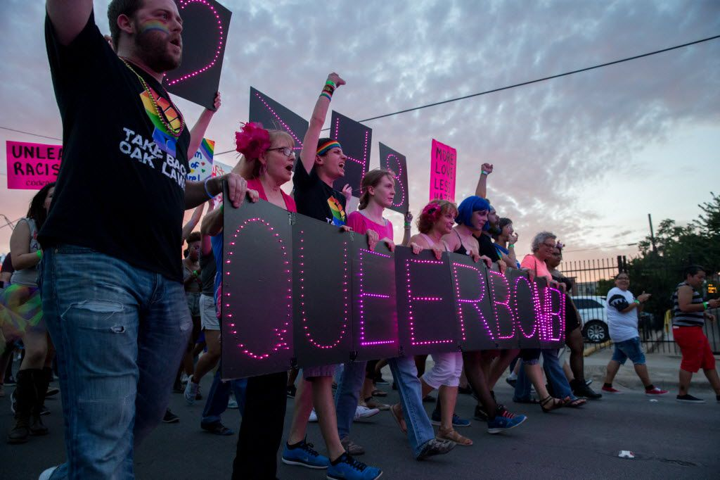 """Attendees of the Queer Bomb Dallas march though Deep Ellum streets with LED signs that display """"Queer Bomb"""" on June 25, 2016 in Dallas. (Ting Shen/The Dallas Morning News)"""