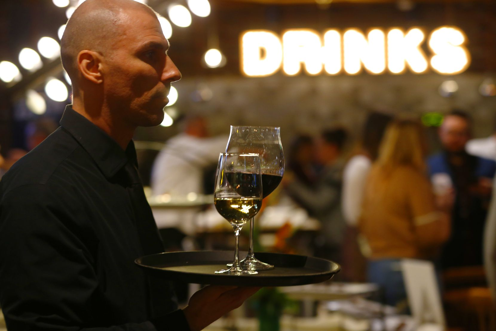 Valerio Dujmovic serves wine at a remodeled and reopened Cafe Express on McKinney Avenue in Uptown.